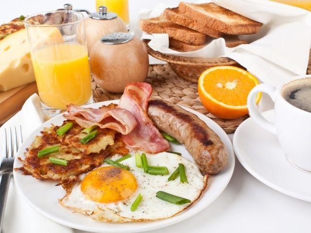 Se observa un brunch típico de Manhattan, contiene zumo de naranja, tostadas, Bacon, huevos y tortitas.