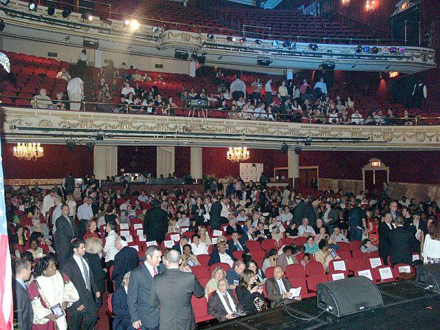 Se observa el interior del edificio apollo teatre con gente en sus butacas.