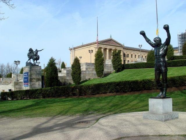 Se observa la estatua de Rocky desde un lateral, al fondo vemos el museo de arte de filadelfia y otra estatua de un jinete.