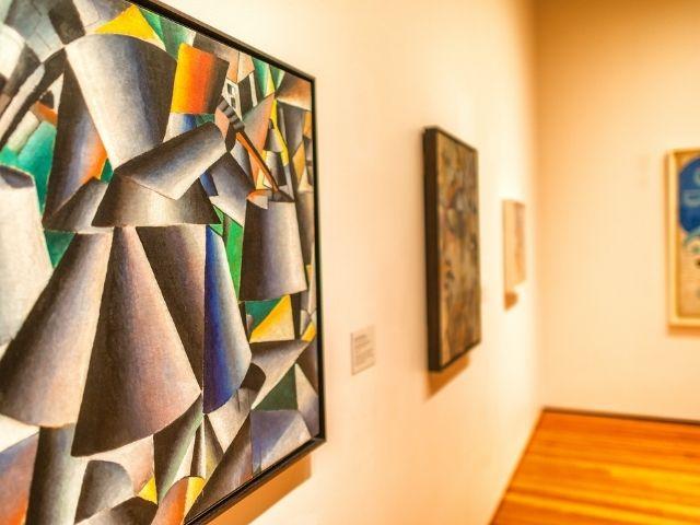 Se observa una parte del interior del Museo MoMa de Nueva York, visualizamos dos cuadros coloridos.