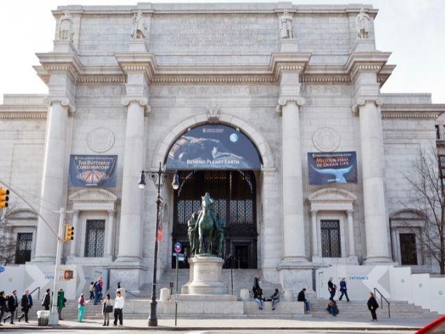 Se observa la entrada al Museo de Historia Natural de Nueva York, en el se observa gente en la entrada y la estatua de Theodore Roosevelt, expresidente de Estados Unidos