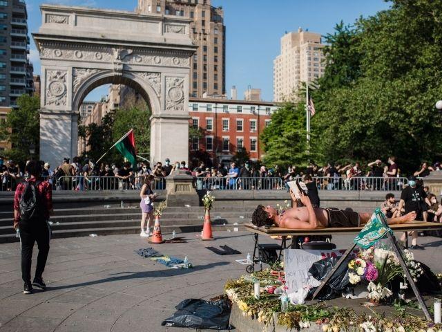 Se observa uno de los mejores parques en Nueva York, el Washington Square Park , en la foto podemos ver todo tipo de personas realizando actividades y detrás en Arco del triunfo.