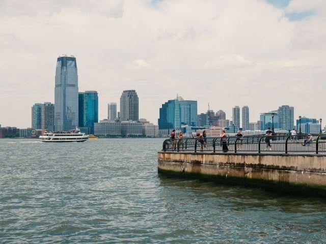 Se observa el SkyLine de New Jersey en Nueva York, vemos a gente en el mirador de la costa y detrás todos los edificios.